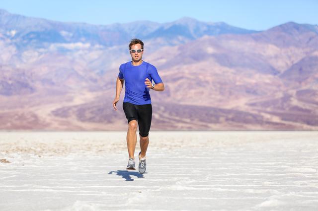 Running man - sprinting athlete runner in desert
